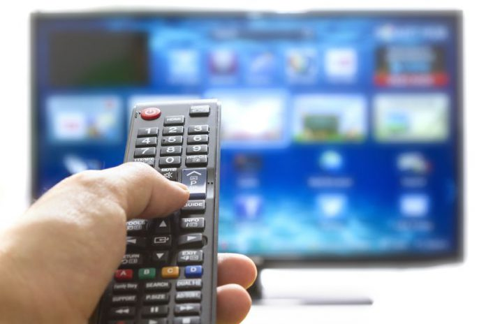17696699 - television remote control changes channels thumb on the blue tv screen