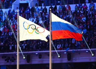 A Russian flag alongside the Olympic flag