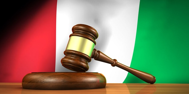 BetConstruct - Law and justice in Italy concept with a 3d rendering of a gavel on a wooden desktop and the Italian flag on background.