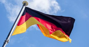 mybet - German flag fluttering in the wind against the blue sky with light clouds, diagonal view from below, soft motion blur