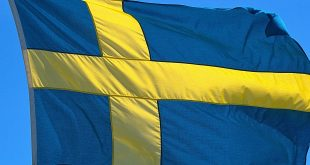 virtual sports - 01.06.2020, Schleswig, the Swedish flag with the yellow Scandinavian cross on a blue background, illuminated by the sun against a blue sky and blowing in the wind. | usage worldwide